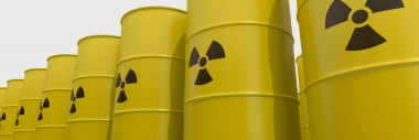 A closeup of a row of yellow barrels with a radioactive symbol printed on them.