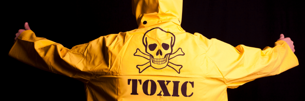 A person from behind with their arms held out horizontal. They are wearing a bright yellow raincoat with a skull & crossbones on the back and the word 'TOXIC'.