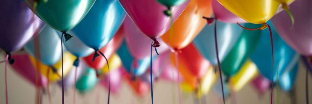 Image shows colourful helium balloons