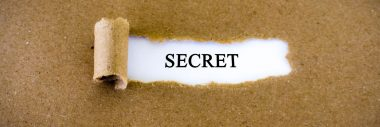 The word secret typed on paper and a strip of fabric being peeled back to reveal the word.