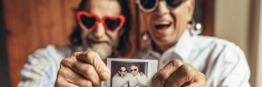 Two older men wearing heart shaped sunglasses and holding out a photo of them together.