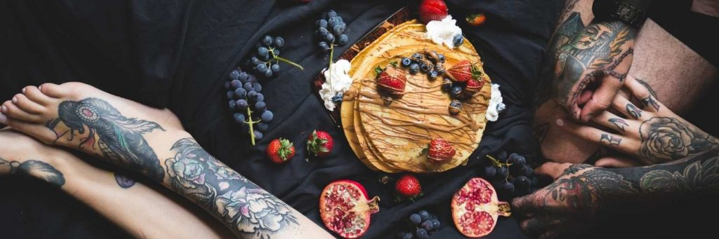 A tattooed couple on a bed. There is a plate of pancakes & berries on the covers.