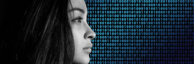 picture of young woman's head in black & white against a background of blue binary code