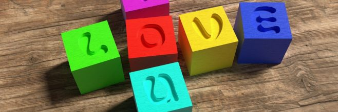 """Coloured blocks on a wooden background that spell Love and You (where they share the letter """"o"""")"""