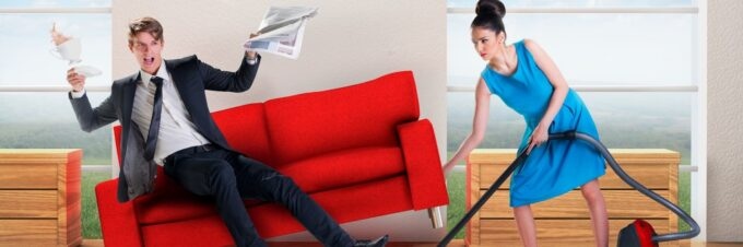 Woman Vacuuming and tipping over couch where man is sitting and reading newspaper.