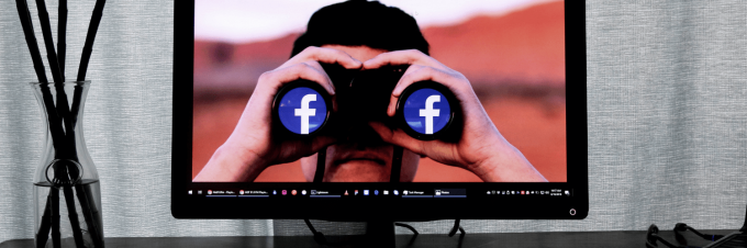 Computer screen with man looking through binoculars that have the facebook logo in each lens.